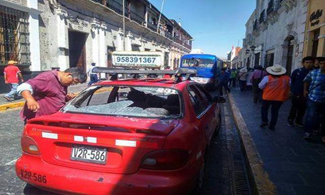 Agresión. Taxista mira como quedó su vehículo. (Foto: HBA Noticias)