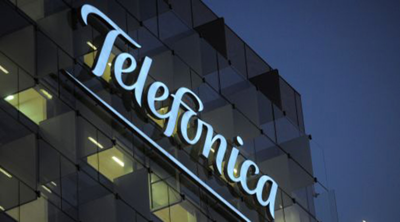 The logo of Telefonica SA hangs illuminated outside the company's headquarters in Madrid, Spain, on Tuesday, Nov. 29, 2011. Telefonica SA, Spain's dominant telecommunications company, aims to complete a review of its online assets such as social networking site Tuenti and the Jajah Web-phone unit early next year. Photographer: Denis Doyle/Bloomberg