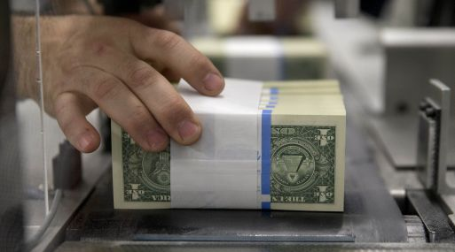 Banded one dollar notes are handled while traveling through a large examining packaging equipment machine at the U.S. Bureau of Engraving and Printing in Washington, D.C., U.S., on Tuesday, April 14, 2015. Republican efforts to pass a fiscal year 2016 budget cleared another hurdle as the House named its members to a conference committee and Senate Majority Leader Mitch McConnell pledged to do the same by the end of the week. Photographer: Andrew Harrer/Bloomberg